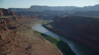 AX138_075 - 6K stock footage aerial video fly over Colorado River through Meander Canyon with view of mesa, Canyonlands National Park, Utah