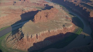 AX138_161 - 6K stock footage aerial video of a reverse view of the Goose Neck in Meander Canyon, Canyonlands National Park, Utah