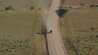 AX138_223 - 6K stock footage aerial video track a silver SUV on Hatch Point Road, Moab, Utah
