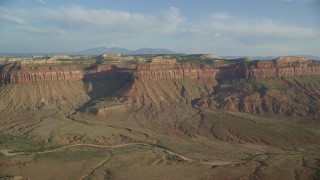 AX138_248 - 6K stock footage aerial video of flying over canyon and dry riverbed to approach mesas, Moab, Utah