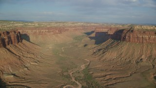 AX138_249 - 6K stock footage aerial video of flying by dry riverbed in a wide desert canyon, Moab, Utah