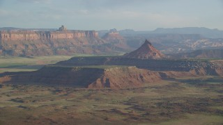 AX138_262 - 6K stock footage aerial video of flying by South SIx-Shooter Peak in a hazy desert valley, Moab, Utah