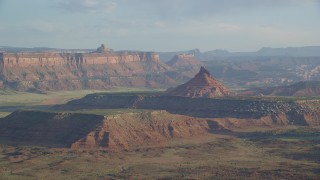 AX138_263 - 6K stock footage aerial video of passing by South Six-Shooter Peak in a hazy desert valley, Moab, Utah