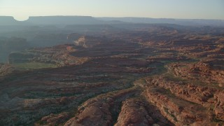 AX138_288 - 6K stock footage aerial video of flying over rock formations and box canyons, Canyonlands National Park, Utah, sunset