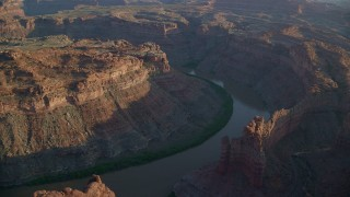 AX138_297 - 6K stock footage aerial video orbiting The Loop West in Meander Canyon and Colorado River, Canyonlands National Park, Utah, sunset