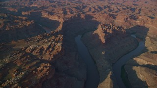 AX138_302 - 6K stock footage aerial video orbit The Loop West, The Loop East parts of Meander Canyon and Colorado River, Canyonlands National Park, Utah, sunset