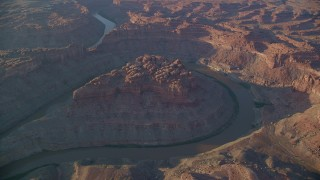 AX138_305 - 6K stock footage aerial video orbiting the river in The Loop East part of Meander Canyon, Canyonlands National Park, Utah, sunset