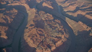 AX138_322 - 6K stock footage aerial video of a bird's eye of the river in Meander Canyon at sunset, Canyonlands National Park, Utah