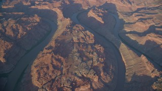 AX138_323 - 6K stock footage aerial video tilt from bird's eye of river in Meander Canyon to The Loop East, Canyonlands National Park, Utah, sunset