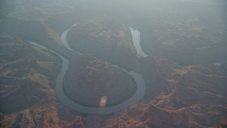 AX138_333 - 6K stock footage aerial video orbit Colorado River through Meander Canyon at sunset, Canyonlands National Park, Utah