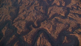 AX138_336 - 6K stock footage aerial video bird's eye view of dry riverbeds through rocky canyons, Canyonlands National Park, Utah, sunset