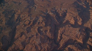 AX138_337 - 6K stock footage aerial video of a bird's eye view of dry riverbeds through rocky canyons, Canyonlands National Park, Utah, sunset