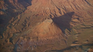 AX138_346 - 6K stock footage aerial video of flying by butte near box canyon in Lockhart Canyon, Moab, Utah, sunset