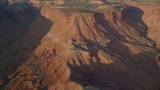 AX138_348 - 6K stock footage aerial video of cliffs, box canyons in hazy Lockhart Canyon, Moab, Utah, sunset