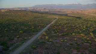 AX138_357 - 6K stock footage aerial video of approaching Hatch Point Road, Moab, Utah, sunset
