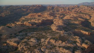 AX138_369 - 6K stock footage aerial video of flying over rock formations and approaching box canyon, Moab, Utah, sunset