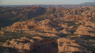 AX138_370 - 6K stock footage aerial video of flying over box canyon and rock formations, Moab, Utah, sunset