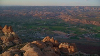 AX138_374 - 6K stock footage aerial video of flying over desert rock formations, revealing small town of Moab, Utah, sunset