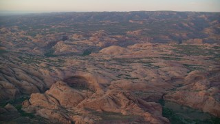 AX138_378 - 6K stock footage aerial video of approaching petrified sand dunes, Sand Flats Recreation Area, Utah, sunset