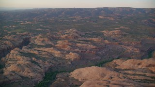 AX138_380 - 6K stock footage aerial video of flying over sand dunes and canyon, Sand Flats Recreation Area, Utah, sunset
