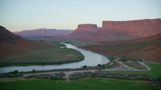 AX138_400 - 6K stock footage aerial video of flying by Red Cliffs Lodge and Colorado River with view of Parriott Mesa, Moab, Utah, sunset