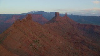 AX138_410 - 6K stock footage aerial video of flying by two buttes and Castleton Tower, Moab, Utah, sunset