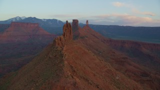 AX138_411 - 6K stock footage aerial video of passing by buttes and Castleton Tower, Moab, Utah, sunset