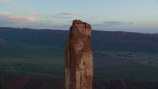 AX138_416 - 6K stock footage aerial video of orbiting Castleton Tower, wide view of valley below, Moab, Utah, sunset