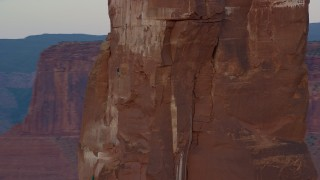 AX138_421 - 6K stock footage aerial video of circling Castleton Tower, revealing rock climber, Moab, Utah, sunset