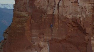 AX138_422 - 6K stock footage aerial video of a rock climber on the side of Castleton Tower, Moab, Utah, sunset