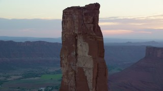 AX138_424 - 6K stock footage aerial video of circling around rock climbers on Castleton Tower, Moab, Utah, sunset