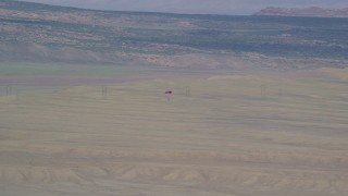 AX139_014 - 6K stock footage aerial video of tracking skydiver descending over desert valley, Canyonlands Field, Utah