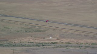 AX139_015 - 6K stock footage aerial video of tracking a skydiver landing in a field, Canyonlands Field, Utah