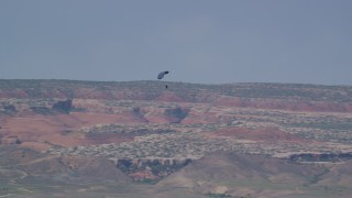 AX139_016 - 6K stock footage aerial video track a skydiver descending into a valley, Canyonlands Field, Utah