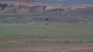 AX139_017 - 6K stock footage aerial video of a skydiver landing in Canyonlands Field, Utah