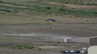AX139_018 - 6K stock footage aerial video of a skydiver landing in a field near buildings, Canyonlands Field, Utah