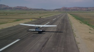 AX139_020 - 6K stock footage aerial video of tracking Cessna taking off from runway, Canyonlands Field, Utah