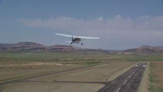 AX139_021 - 6K stock footage aerial video of tracking Cessna ascending over runway, Canyonlands Field, Utah