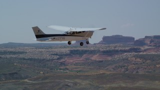 AX139_024 - 6K stock footage aerial video of tracking Cessna flying over a desert, Grand County, Utah