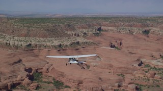 AX139_028 - 6K stock footage aerial video of tracking a Cessna over desert and approaching rock formations, Grand County, Utah