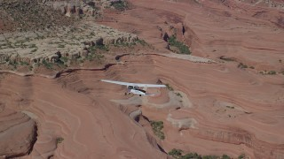 AX139_029 - 6K stock footage aerial video of a Cessna over desert approaching rock formations, Grand County, Utah