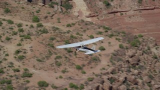 AX139_030 - 6K stock footage aerial video of a Cessna over desert rock formations, Grand County, Utah