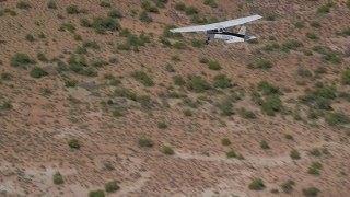 AX139_031 - 6K stock footage aerial video track a Cessna flying over desert in Grand County, Utah