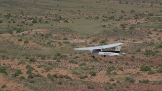 AX139_032 - 6K stock footage aerial video of tracking a Cessna as it flies over desert, Grand County, Utah