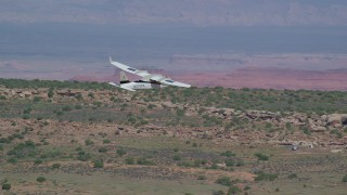 AX139_033 - 6K stock footage aerial video of tracking a Tecnam P2006T over desert, Grand County, Utah