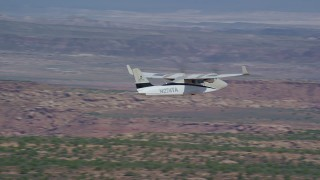 AX139_035 - 6K stock footage aerial video track a Tecnam P2006T flying over desert valley, Grand County, Utah