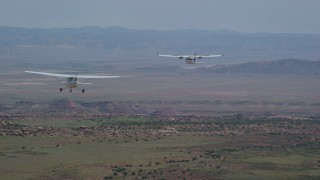 AX139_036 - 6K stock footage aerial video of tracking Tecnam P2006T over desert, zoom to reveal Cessna, Grand County, Utah