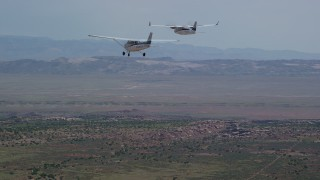 AX139_037 - 6K stock footage aerial video of tracking Tecnam P2006T and Cessna flying over desert, Grand County, Utah