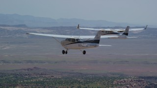 AX139_038 - 6K stock footage aerial video of tracking Tecnam P2006T and Cessna flying over a desert, Grand County, Utah