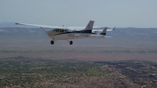 AX139_039 - 6K stock footage aerial video of Tecnam P2006T and Cessna flying over desert, Grand County, Utah